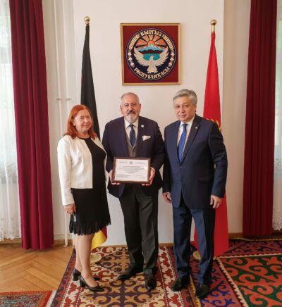 Moment wręczenia podziękowania za wieloletnie zaangażowanie się Konsula Janusza Krzywoszyńskiego na rzecz Republiki Kirgiskiej i jej obywateli.